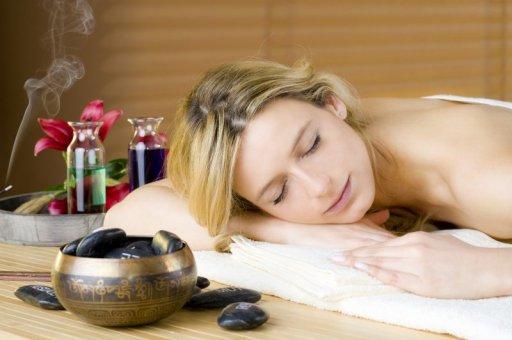 Eine junge Frau entspannt während einer Massage in schönem Ambiente: Räucherduft, Hot Stones und eine Schale sind zu sehen.